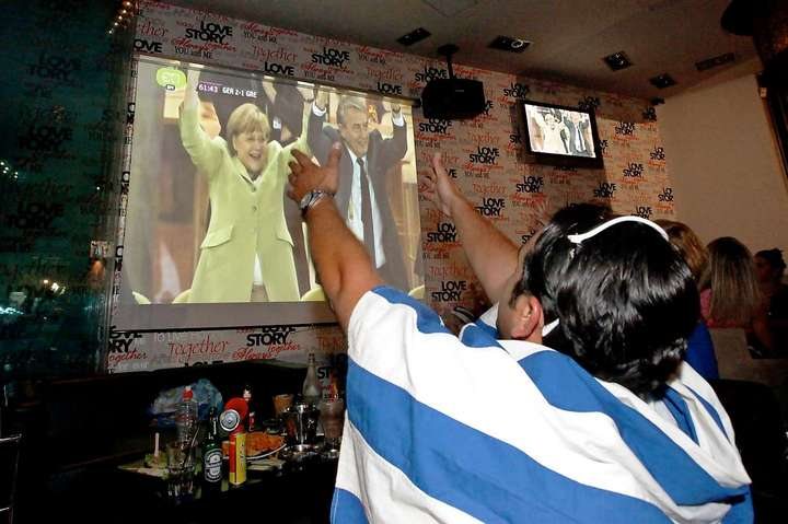 A Greece soccer fan watches German Chancellor Angela Merkel celebrating on screen over the EURO 2012 quarter-final match between Germany and Greece, at a cafeteria in Athens