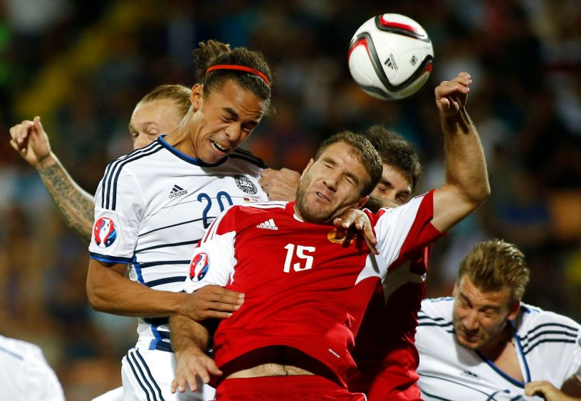 Armenia's Hrayr Mkoyan (C) jumps for a header with Denmark's Yussuf Poulsen (L) during their Euro 2016 group I qualification match at the Vazgen Sargsyan Republican stadium in Yerevan, Armenia, September 7, 2015. REUTERS/David Mdzinarishvili